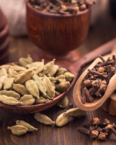 Clove and cardamom spices in scoops still-life